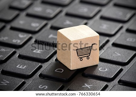 Wooden block with shopping cart graphic on laptop keyboard. 3D illustration. Online shopping concept.