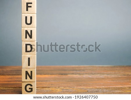 Wooden block with the word Funding. The concept of providing financial resources to organizations and enterprises. Credit, donations, taxes, grants, savings and subsidies. Business and finance Stock photo ©