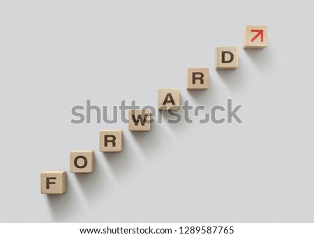 Wooden blocks arranged in stair shape with the word FORWARD. Moving forward, business growth or mindset concept.