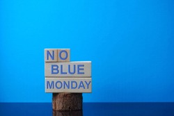 Wooden blocks arranged with the words NO BLUE MONDAY on blue background. Image contains soft focus and selective focus