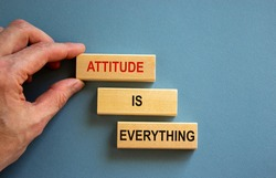 Wooden blocks form the words 'attitude is everything' on blue background. Male hand.