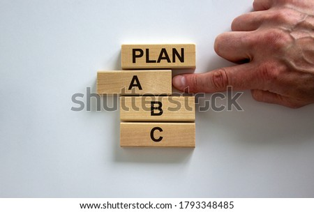 Wooden blocks form the words 'plan, A, B, C' on white background. Male hand. Beautiful background. Business concept, copy space. Foto stock ©