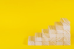 Wooden blocks forming stairway on yellow background. Ladder of success, business investment growth, success or career path success concept. Personal development
