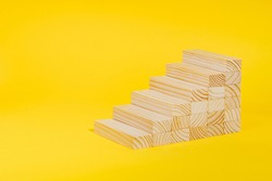 Wooden blocks forming stairway on yellow background. Personal growth, business career path concept. Ladder of success, investment, development .
