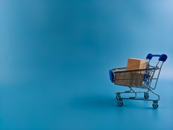 Wooden blocks in a trolley isolated blur background. Shopping online and add to cart concept.