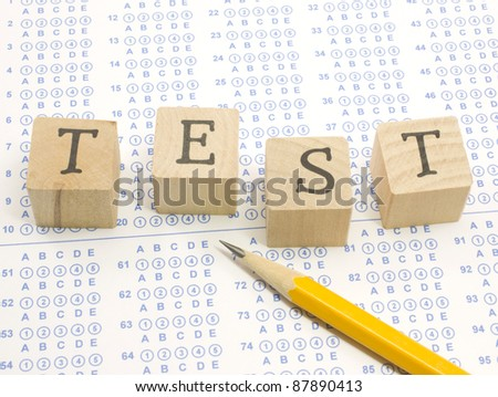 Wooden blocks spell out TEST on a blue bubble or scantron sheet with a number two yellow pencil.