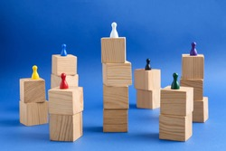 Wooden blocks with color playing pieces on blue background. Roles and responsibility concept