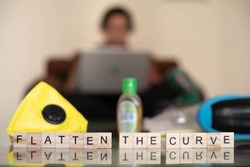 Wooden blocks with flatten the curve with an out of focus background of a young indian girl woman working on her phone laptop while working from home on a self imposed quarantine in the corona covid