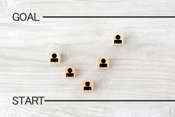 Wooden blocks with human pictogram arranged by starting line