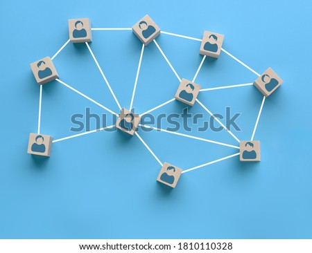 Wooden blocks with people icon interconnected by white lines on blue background. Cooperation, teamwork, business training concept. Social connections, joining to solve tasks Stockfoto ©