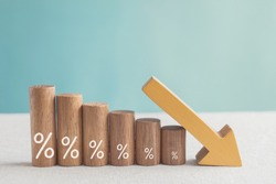 Wooden blocks with percentage sign and down arrow, investment reduce, financial recession crisis, interest rate decline, risk management concept