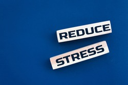 Wooden blocks with Reduce Stress text and blue background. Concept image to keep calm and stop worrying. Healthcare concept.