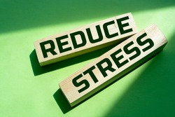 Wooden blocks with Reduce Stress text and green background. Concept image to keep calm and stop worrying. Healthcare concept.