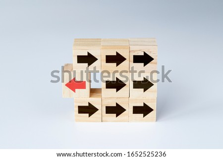 Wooden blocks with several black arrows and one block with red arrow facing the opposite direction. Concept photo of uniqueness, thinking different, individualism and standing out from the crowd.