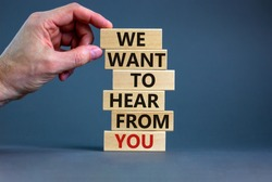 Wooden blocks with text 'we want to hear from you'. Male hand. Beautiful grey background, copy space. Business concept.