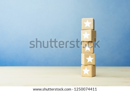 Wooden blocks with the five star symbol on the table, evaluation, Increase rating, Customer experience, satisfaction and best excellent services rating concept. #1250074411