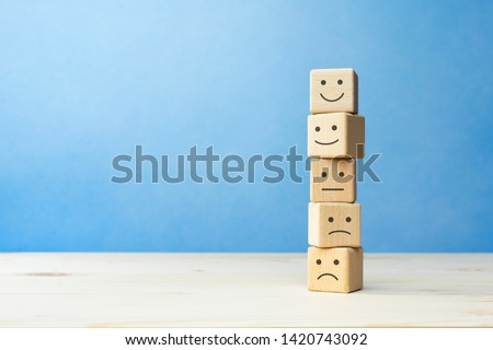 Wooden blocks with the happy face smile face symbol symbol on the table, evaluation, Increase rating, Customer experience, satisfaction and best excellent services rating concept with copy space