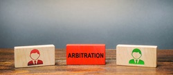 Wooden blocks with the image of two people and the word Arbitration between them. Alternative dispute resolution. Resolve disputes outside the judiciary courts. Conciliation, mediation, negotiation