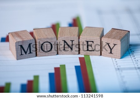 Wooden blocks with the lettering Money on top of ascending bar graphs analyzing the statics and performance of shares within the market