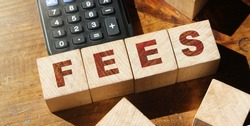 Wooden Blocks with the text: Fees and calculator on wooden table. Taxes and fees business financial concept.