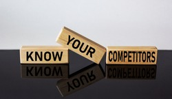 Wooden blocks with the text KNOW YOUR COMPETITORS on a white and black background.