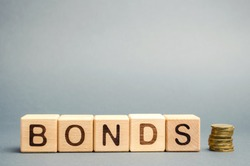 Wooden blocks with the word Bonds and coins. A bond is a security that indicates that the investor has provided a loan to the issuer. Equivalent loan. Unsecured and secured bonds