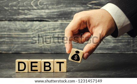 Wooden blocks with the word debt and the image of dollars. Payment of taxes and of debt to the state. Concept of financial crisis and problems. Risk management. Debt exemption. loan