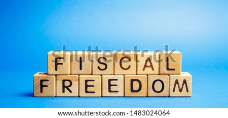 Wooden blocks with the word Fiscal freedom. Tax burden imposed by government. Taxation. Taxes concept. Business and Finance #1483024064