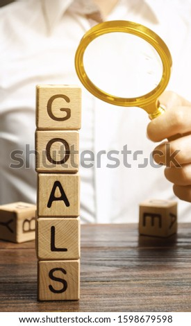 Wooden blocks with the word Goals and businessman. The concept of achieving business goal. Reaching new heights. Execution of a business plan. Purposefulness. Perseverance. Target. Planning