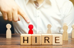 Wooden blocks with the word Hire. Headhunter selects a person from the crowd. Good choice. Human Resource Management. Recruiting Headhunting. Hiring employees. Businessman's hand points to the red man