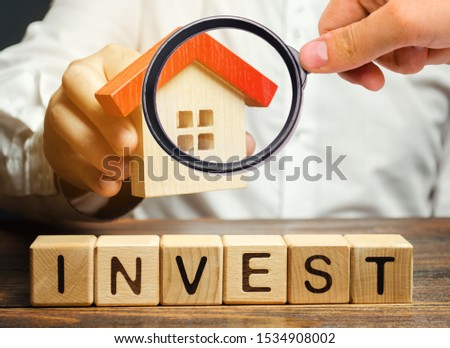 Wooden blocks with the word Invest and house in the hands of a businessman. The concept of investing in real estate construction. Effective investment. Buying apartments. Business and finance #1534908002