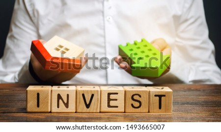 Wooden blocks with the word Invest and houses in the hands of a businessman. The concept of investing in real estate construction. Effective investment. Buying apartments. Business and finance