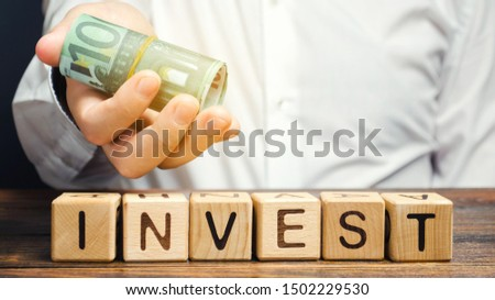 Wooden blocks with the word Invest and money in the hands of a businessman. Concept of investing in a business project. Economics and finance. Cash investments for profit