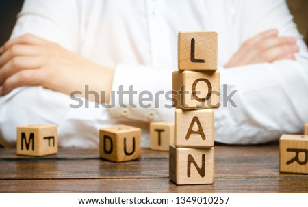 Wooden blocks with the word loan and businessman. Consumer, banking and property loan. Business and entrepreneurial development. Small business loans. Interest rate repayment. Planning