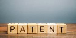 Wooden blocks with the word Patent. Form of intellectual property. Document attesting the right of an inventor to his invention.