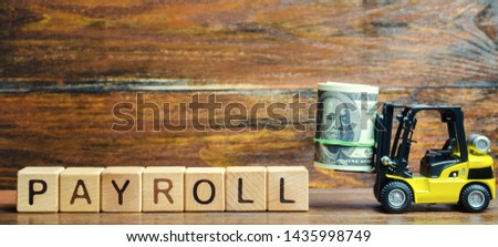 Wooden blocks with the word Payroll, money and a forklift. Payroll is the sum total of all compensation a business must pay to its employees for a set period of time or on a given date. Taxes.