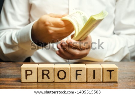 Wooden blocks with the word Profit and a man who counts money. The financial result of the company for a certain period of time. Income. Return on investment. Performance. Profitable business. ROR ROI #1405515503