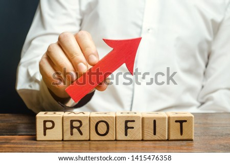Wooden blocks with the word Profit and an up arrow. Concept of business success, financial growth and wealth. Increase profits and investment fund. Performance. Profitable business. ROR, ROI #1415476358