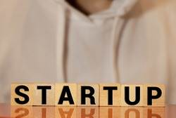 Wooden blocks with the word Startup. Temporary structure designed to find and implement a scalable business model. The concept of raising funds for a startup. Crowdfunding. Investing in the future.