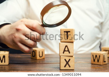 Wooden blocks with the word Tax and a magnifying glass in the hands of a businessman. The concept of studying the size of taxes. Taxation. Time to pay taxes. Tax on personal income. Agent. Taxpayer Stock photo ©
