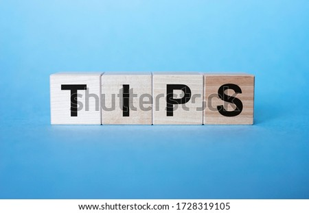 Wooden blocks with the word Tips on blue background. Award for good service in the cafe restaurant. A gratuity is a sum of money customarily given by a client or customer to a service worker Сток-фото ©