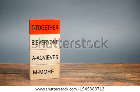 Wooden blocks with the word Together, Everyone, Achieves, More. Teamwork and team concept. Community, support, partnership. Achieving a common goal. Cooperation and business strategy