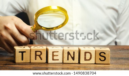 Wooden blocks with the word Trends and businessman with a magnifying glass. Popular and relevant topics. New ideological trends. Recent and latest trend. Evaluation methods.