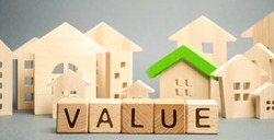 Wooden blocks with the word Value and wooden houses. Property valuation and housing. The best value of the apartment or house for sale. Home appraisal. Real estate market. Mortgage rates