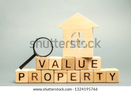 Wooden blocks with the word Value Property and the house with a magnifying glass. The study of the state of the house / housing. Home Inspection / valuation. Appraisal real estate