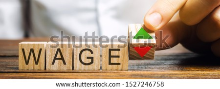 Wooden blocks with the word Wage and up and down arrows. The concept of unstable wages. Business and finance. Income, salary, revenue Stock photo ©