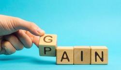 Wooden blocks with the words Gain, pain. Motivation, aspiration, goal achievement concept. Management and change