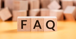 Wooden blocks with word FAQ on yellow baclground. Frequently asked question concept