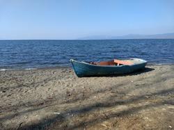 Wooden blue rowboat on the shore of the Lake Iznik, lake view under the blue sky in Iznik, Bursa - Turkey