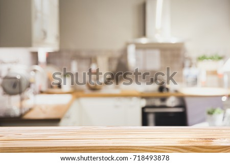 Photo of Wooden board empty table in front of Blur image of modern Kitchen Room interior - can be used for display or montage your products.Mock up for display of product.